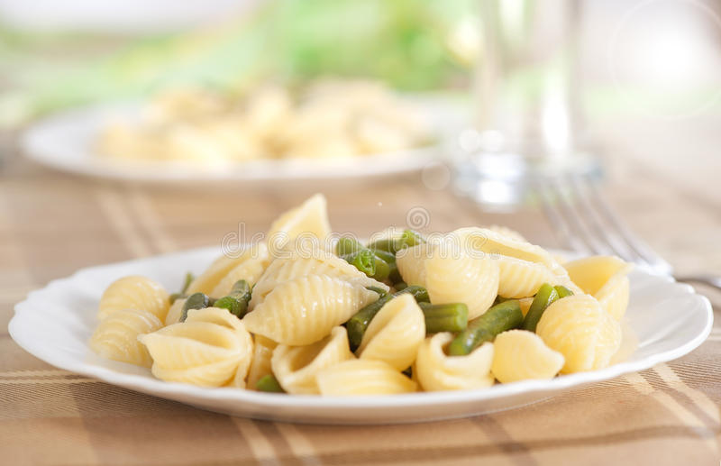 Pasta with green beans. On a plate stock image