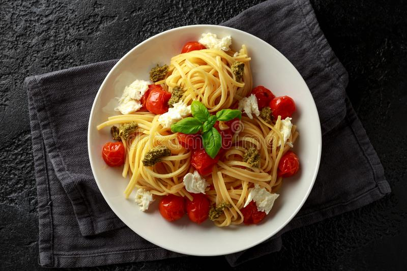 Pasta with green pesto sauce, roasted cherry tomatoes and mozzarella cheese in white plate on dark rustic background royalty free stock photos