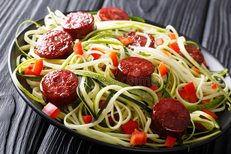Pasta of green zucchini with red pepper and grilled sausages close-up. horizontal royalty free stock photo