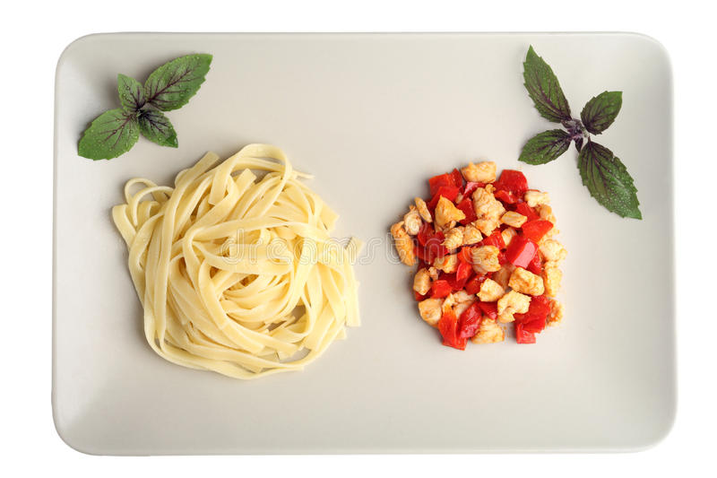 Pasta with grilled chicken and peppers. Pasta on a white backgrou royalty free stock image