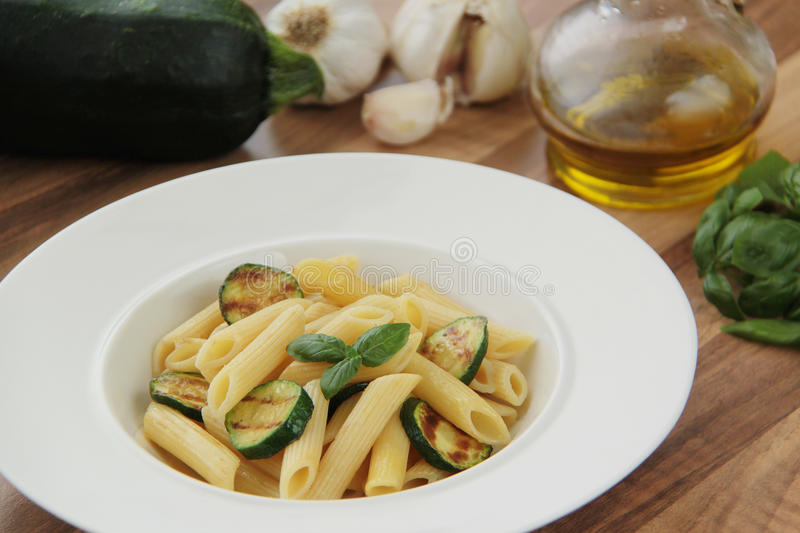 Pasta with grilled slices of zucchini, garlic, basil herb and olive oil. Ingredients for cooking on background. Close up view. stock images