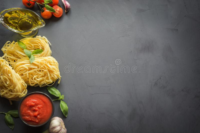 Pasta ingredients for cooking Italian dishes, tagliatelle, tomatoes, basil, oil and garlic. Food pattern. Top view with space for stock photography