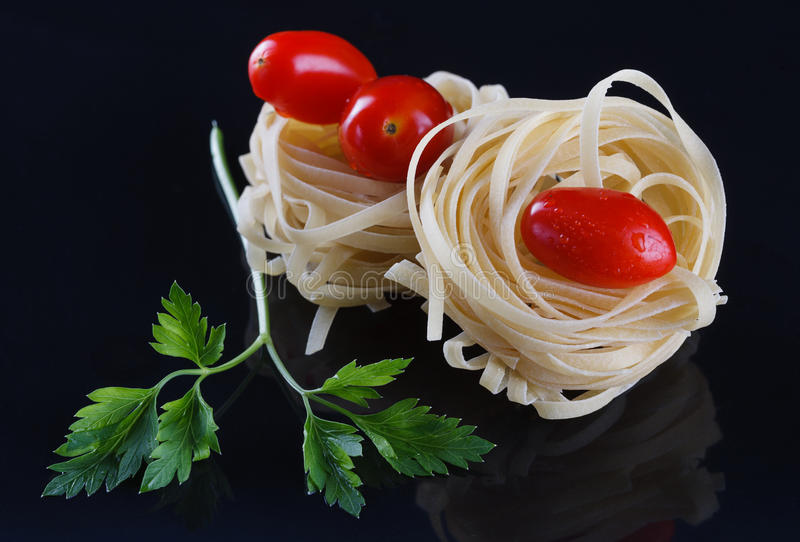 Pasta ingredients. Spaghetti nests, cherry tomatoes and parsley on a black reflective background royalty free stock images