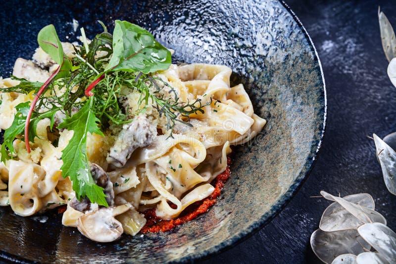 Pasta italiana casalinga fresca con i funghi della foresta, la salsa del tartufo ed il parmigiano Fuoco selettivo del primo piano immagine stock