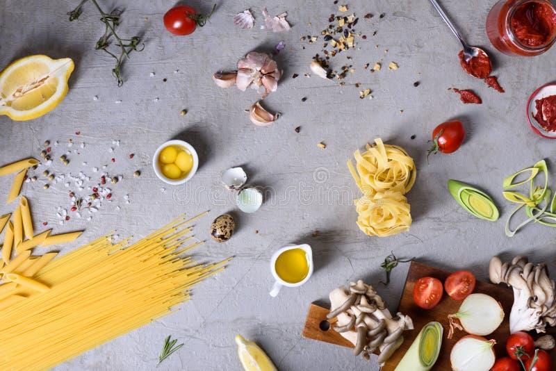Pasta italiana con la cottura degli ingredienti Paste, spezie, salsa al pomodoro e verdure sopra fondo grigio Vista superiore, sp fotografia stock libera da diritti