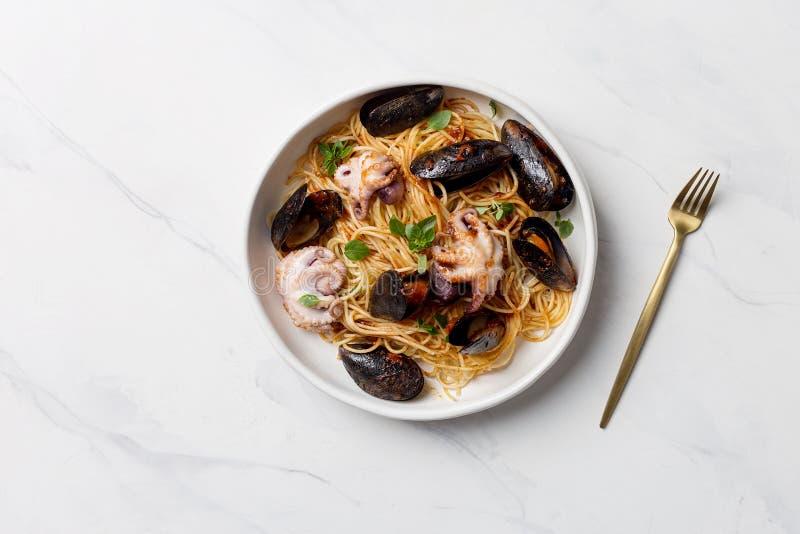 Pasta italiana con le cozze ed il polipo in piatto bianco fotografia stock