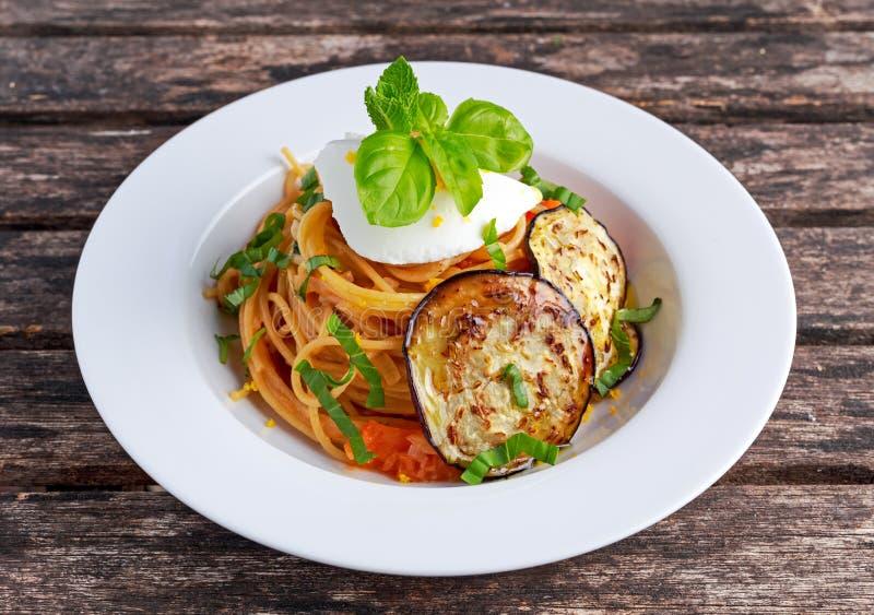 Pasta italiana con le melanzane, il pomodoro, il formaggio di ricotta ed il basilico immagini stock
