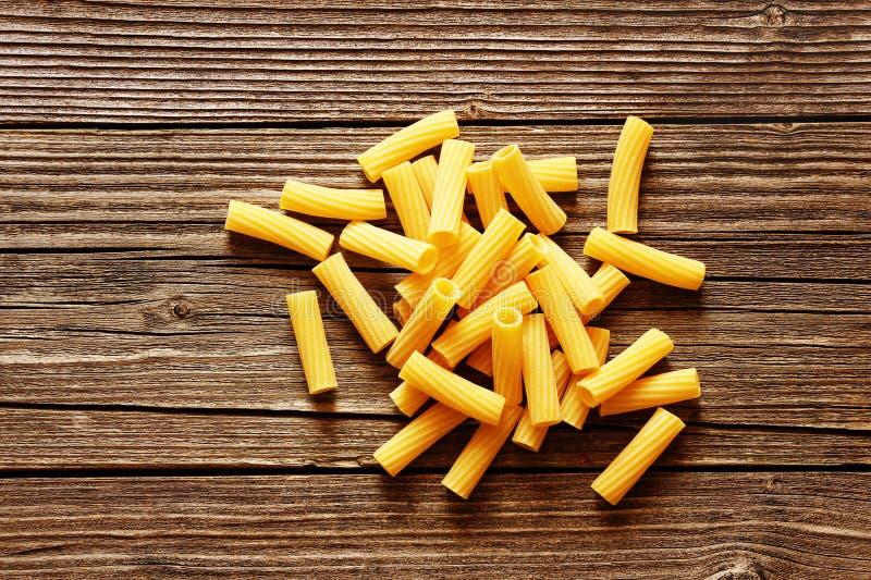 Pasta italiana gialla su un fondo rustico di legno fotografie stock libere da diritti