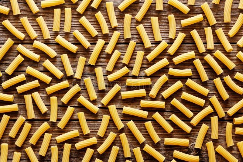 Pasta italiana gialla su un fondo rustico di legno immagine stock