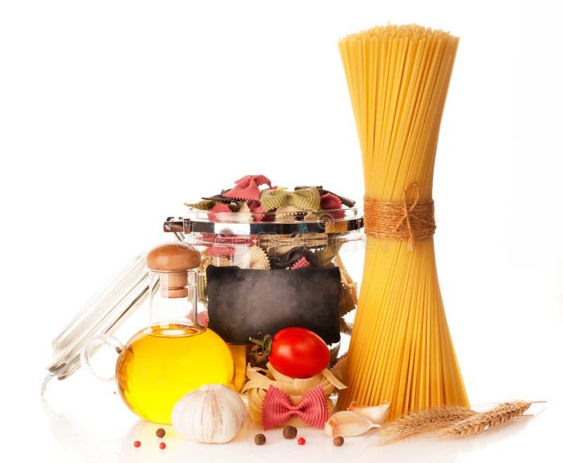 Pasta italiana, spaghetti, farfalle in un vaso d'annata, pomodori, aglio e spezie. fotografia stock libera da diritti