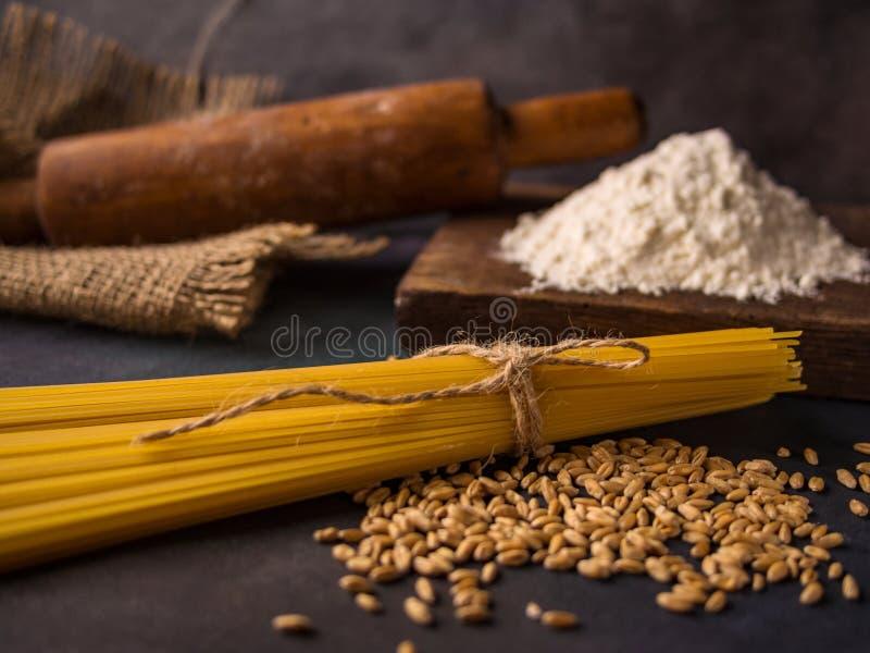 Pasta italiana, spaghetti, grano, matterello, farina su un fondo strutturato Ancora vita in uno stile rustico Elemento per proget fotografia stock libera da diritti