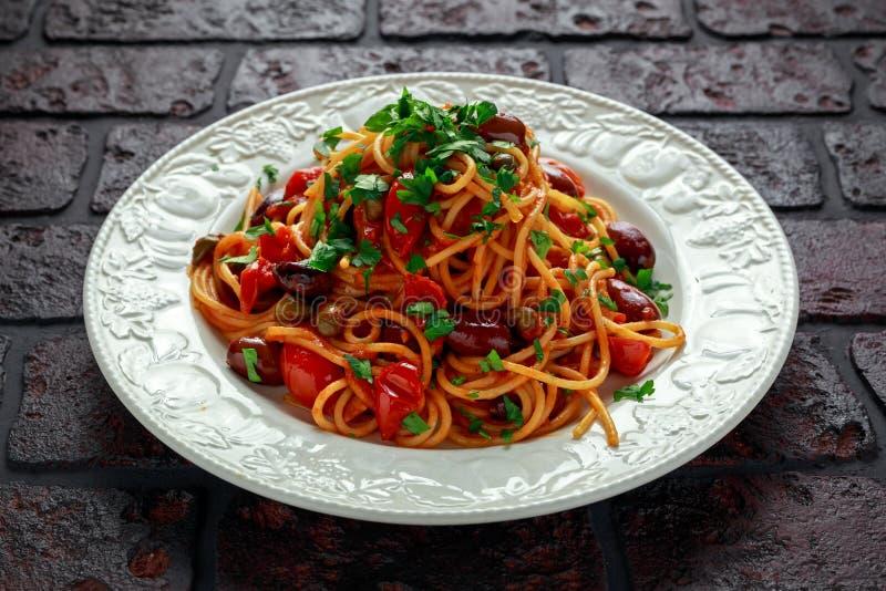 Pasta italiana vegetariana Alla Puttanesca con aglio, olive, capperi con sul piatto bianco fotografia stock libera da diritti