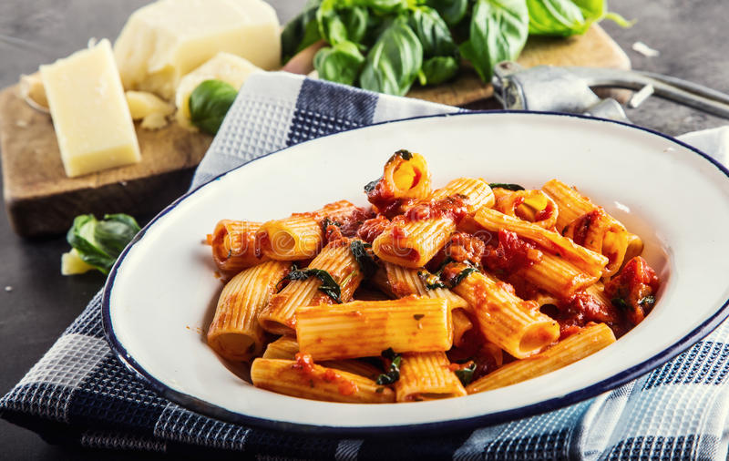 Pasta Italienare- och Mediterrannean kokkonst Pasta Rigatoni med basilika för tomatsås lämnar vitlök- och parmesanost royaltyfri foto