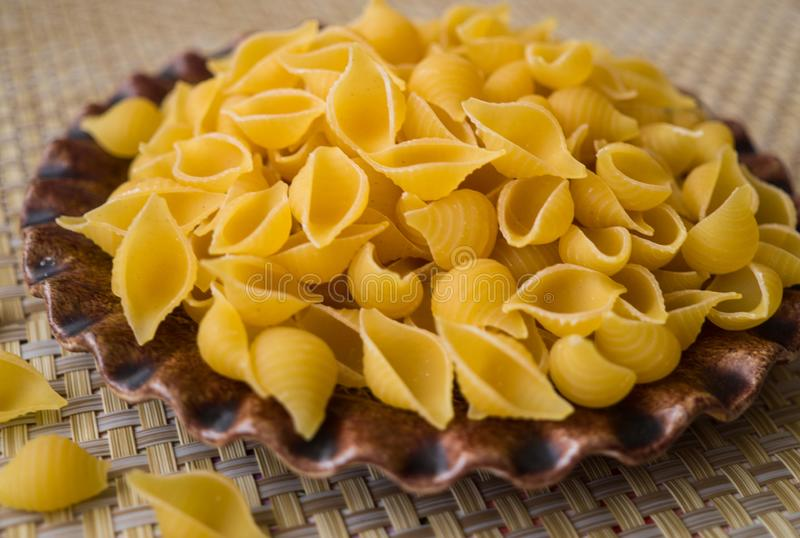 Pasta made from flour, scattered on a plate, on a table stock images