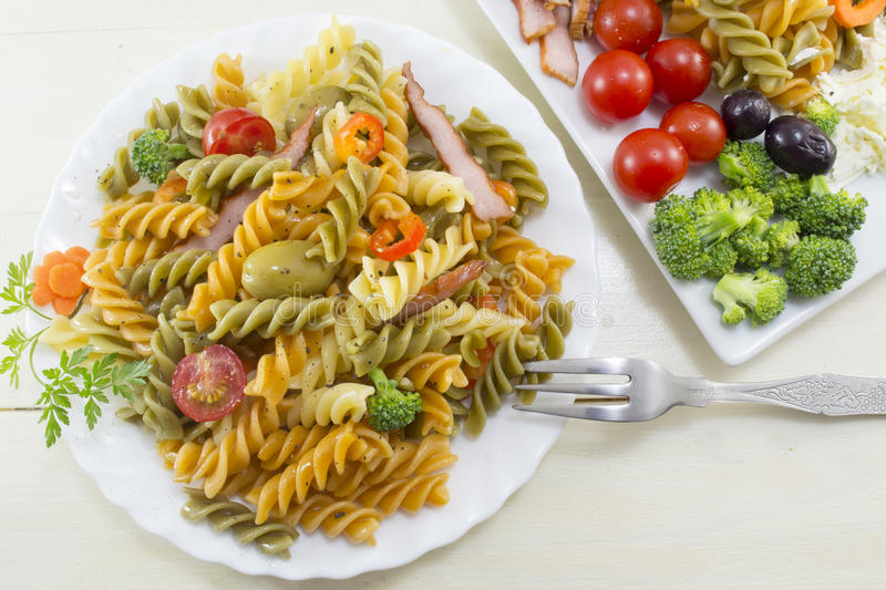 Pasta meal cooked with vegetables with fresh vegetables served o. Pasta meal cooked with vegetables with fresh vegetables served in white dishes royalty free stock images