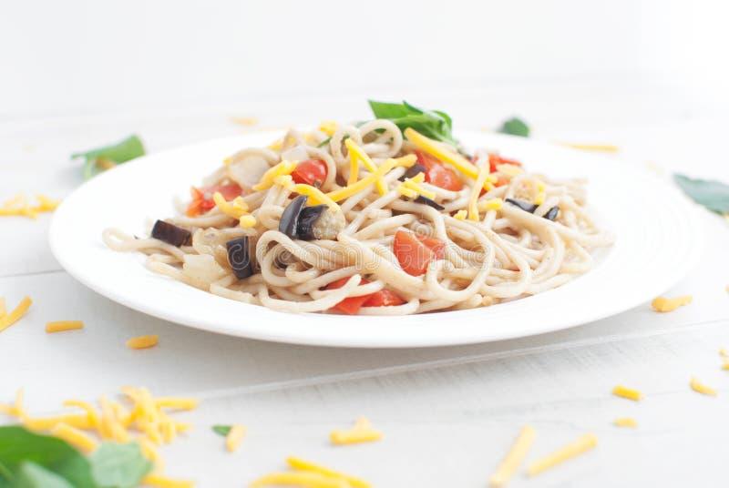 Pasta med aubergine, Cherrytomater och vitlök royaltyfria foton