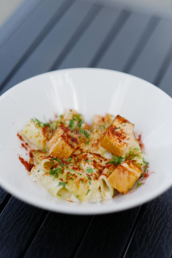 Pasta med den röda fisken i en vit platta på tabellen arkivbild