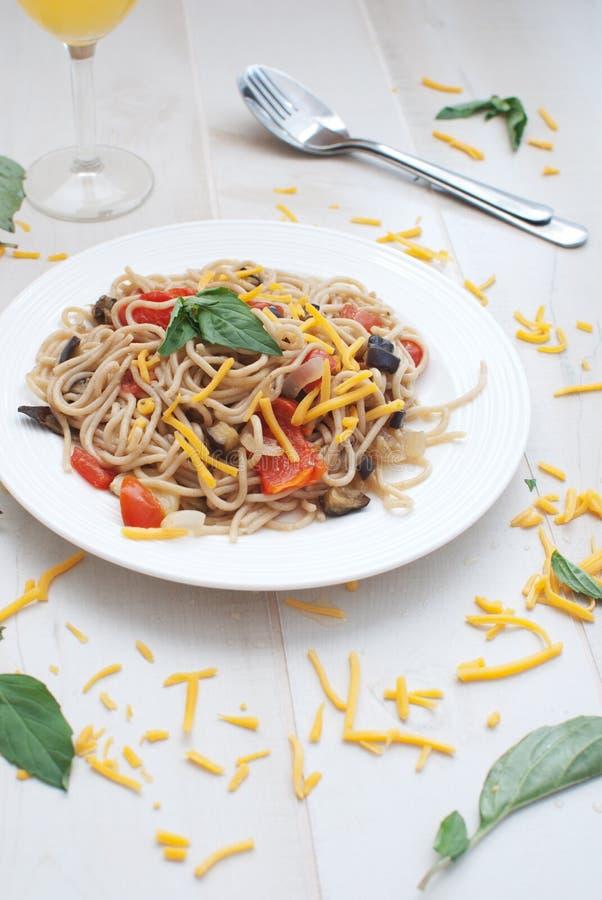 Pasta med grönsaker och ett exponeringsglas av fruktsaft royaltyfri bild