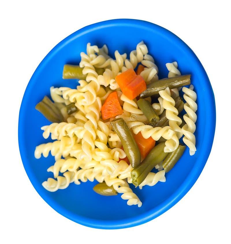 Pasta med haricot vert med garlicandmorötter på en platta som isoleras på en vit bakgrund medelhavs- k?k B?sta sikt f?r pasta arkivbilder