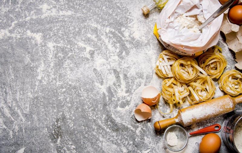 Pasta med ingredienser - mjöl, ägg och olika hjälpmedel för att laga mat arkivfoto