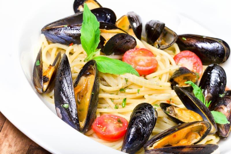 Pasta med musslor och basilika för en smaklig makro för mål för havsmat arkivfoto