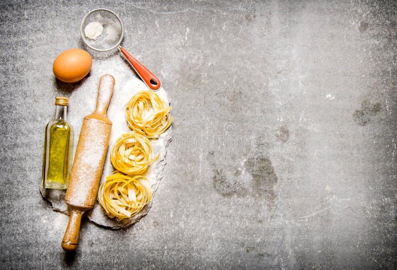 Pasta med olivolja, sikten, kavlen och mjöl på en sten står arkivbild