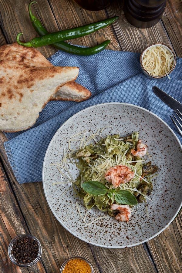 Pasta med räkor och basilikasås Italiensk kokkonst f?r begrepp Traditionell italiensk pasta med räkor och basilika, olivolja royaltyfria bilder