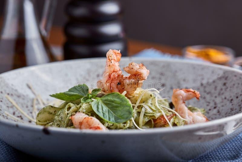 Pasta med räkor och basilikasås Italiensk kokkonst f?r begrepp Traditionell italiensk pasta med räkor och basilika, olivolja royaltyfri fotografi
