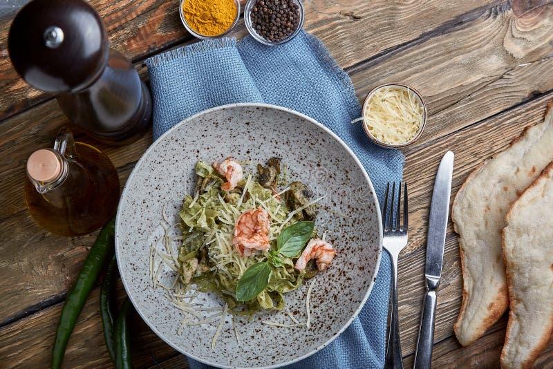 Pasta med räkor och basilikasås Italiensk kokkonst f?r begrepp Traditionell italiensk pasta med räkor och basilika, olivolja royaltyfri bild