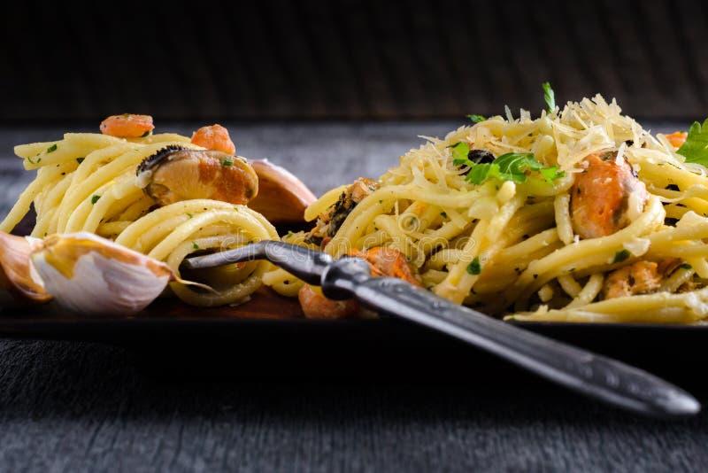 Pasta med räkor och musslor i krämig sås på en platta på ett D royaltyfria bilder
