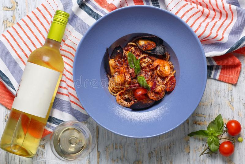 Pasta med skaldjur och en flaska av vin royaltyfri fotografi