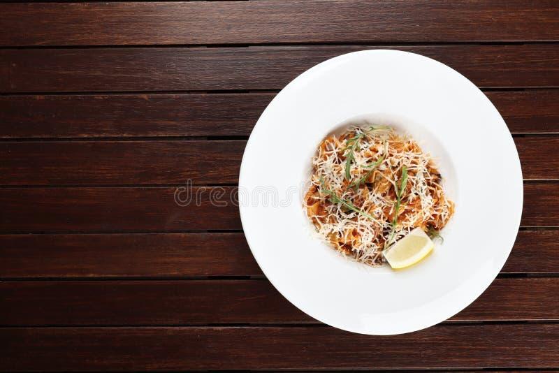 Pasta med skaldjur- och parmesanost finns på en träbakgrund royaltyfria bilder