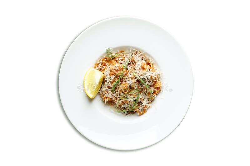 Pasta med skaldjur- och parmesanost finns på en vit bakgrund royaltyfri bild