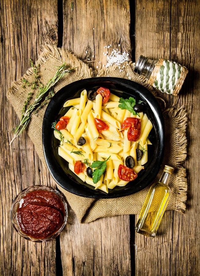 Pasta med tomater, oliv och örter arkivbild
