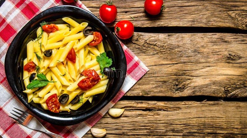 Pasta med tomater, oliv och örter royaltyfri bild