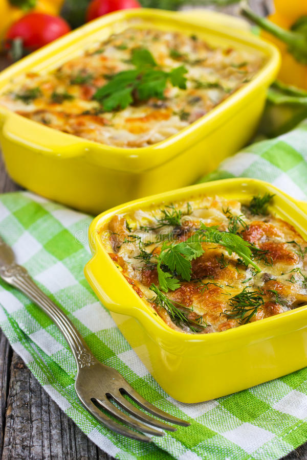 Pasta, mushrooms and cheese gratin. In casserole dish stock photos