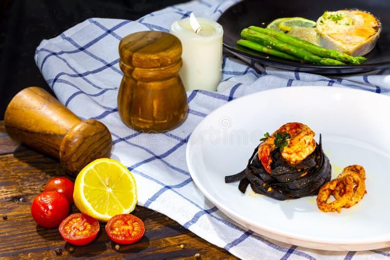 Pasta nera degli spaghetti del fettuccine con il topp del gamberetto e del calamaro della roccia fotografia stock libera da diritti
