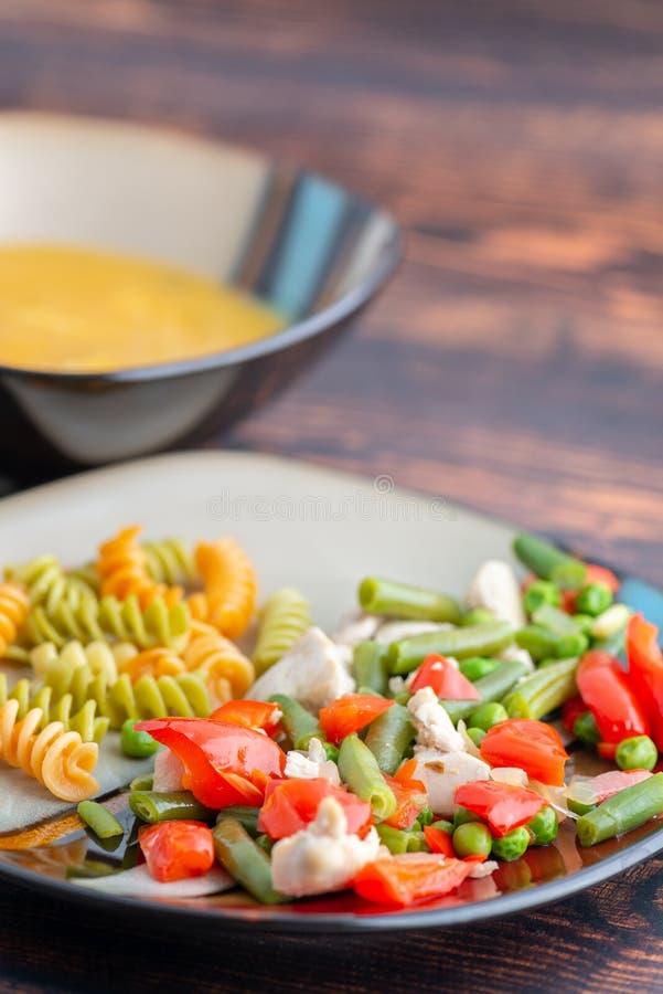 Pasta och höna med grönsaker på platta- och pumpasoppa royaltyfria bilder