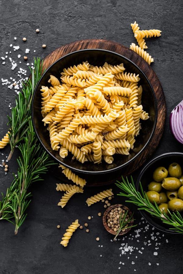 Pasta och ingredienser för att laga mat på svart bakgrund, bästa sikt italienska matlagningmatingredienser royaltyfri fotografi