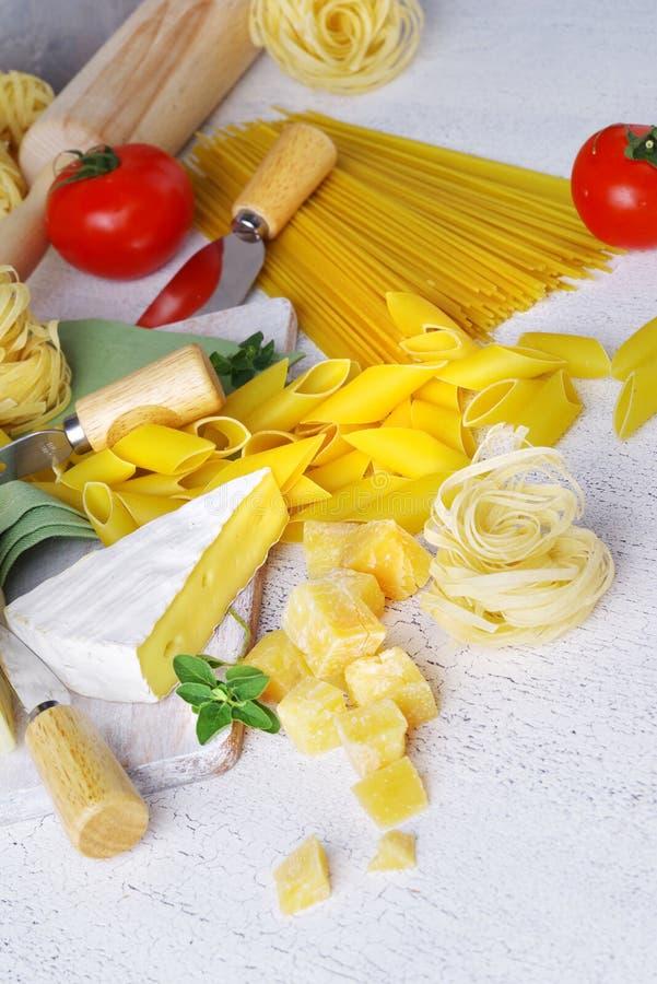 Pasta och ost med olika ingredienser för att laga mat på en ljus lantlig bakgrund fotografering för bildbyråer
