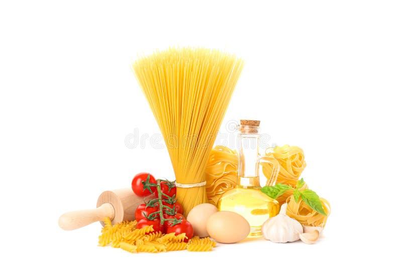 Pasta, olivolja, tomater, ägg, kavel och vitlök som isoleras på vit bakgrund royaltyfri bild