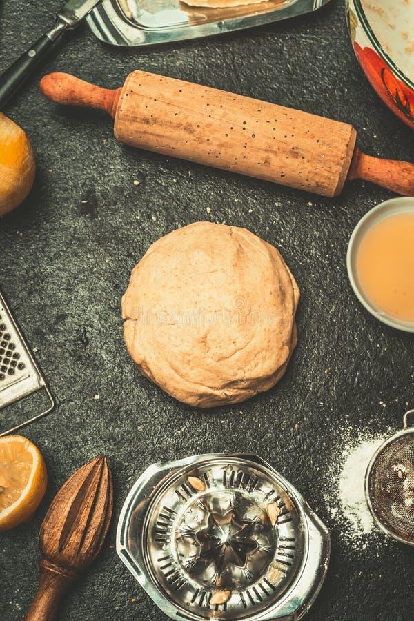 Pasta para las galletas u hornada de la torta en fondo oscuro de tabla de cocina con los peajes y los ingredientes imagen de archivo libre de regalías