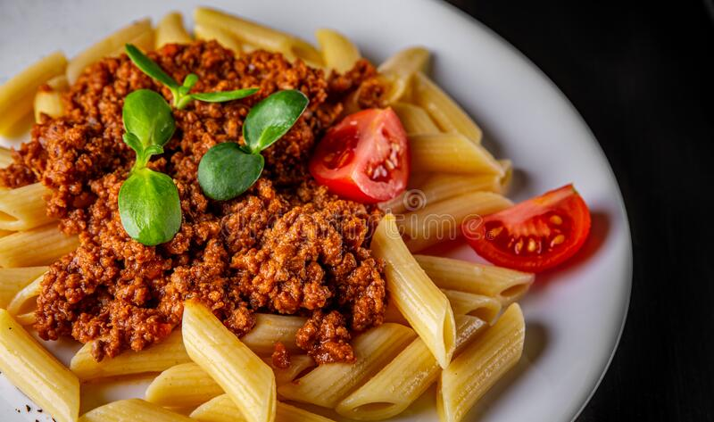 Pasta penne bolognese in white plate on black wooden table stock photography