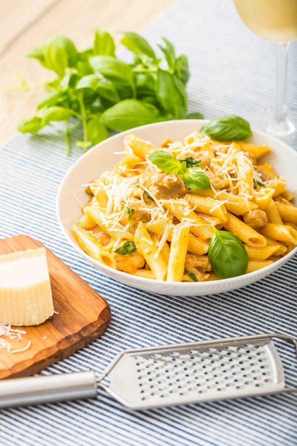Pasta penne with chicken pieces mushrooms basil parmesan cheese and white wine. Italian food in white plate on kitchen royalty free stock images
