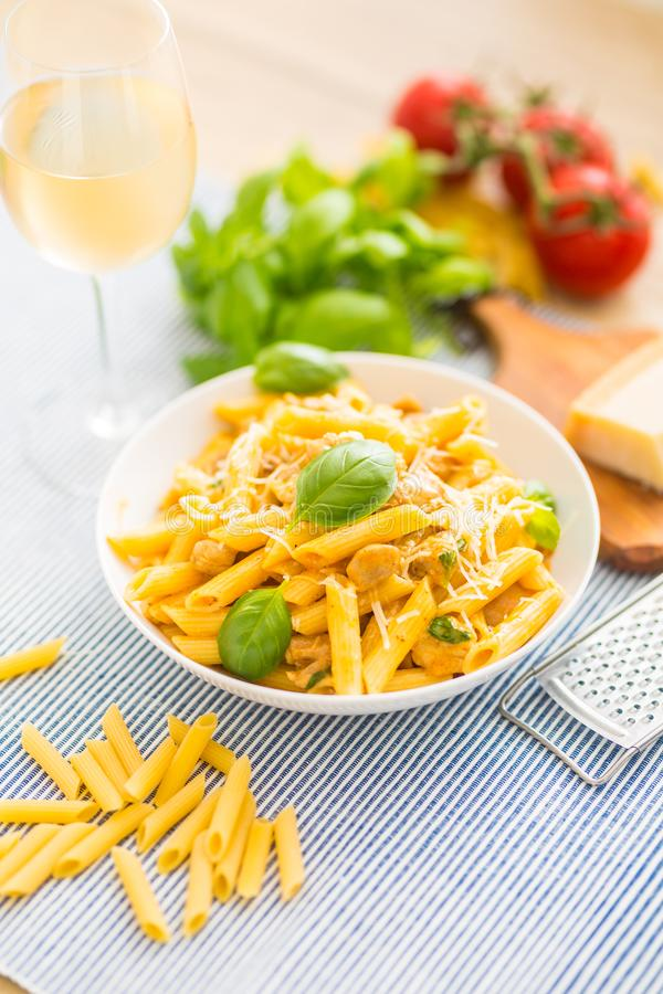 Pasta penne with chicken pieces mushrooms basil parmesan cheese and white wine. Italian food in white plate on kitchen. Pasta penne with chicken pieces mushrooms royalty free stock images
