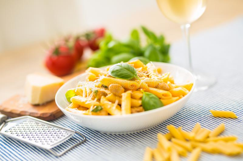 Pasta penne with chicken pieces mushrooms basil parmesan cheese and white wine. Italian food in white plate on kitchen. Pasta penne with chicken pieces mushrooms stock photo