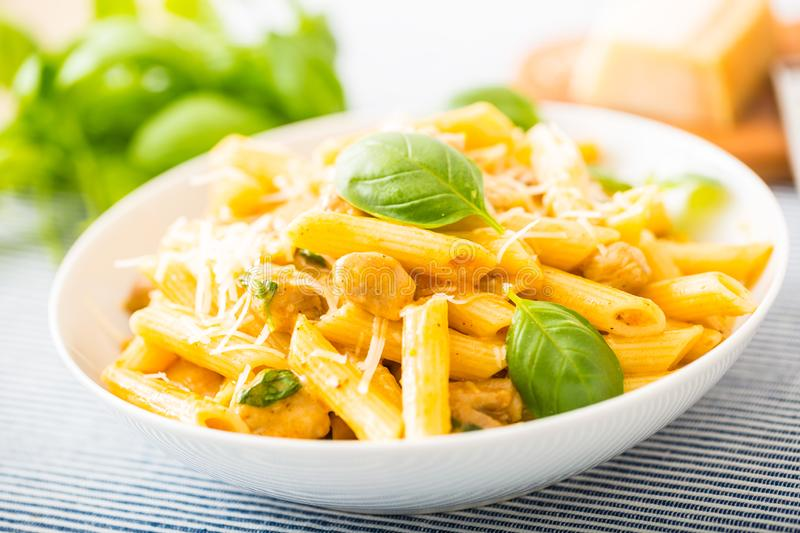 Pasta penne with chicken pieces mushrooms basil parmesan cheese and white wine. Italian food in white plate on kitchen. Pasta penne with chicken pieces mushrooms stock images