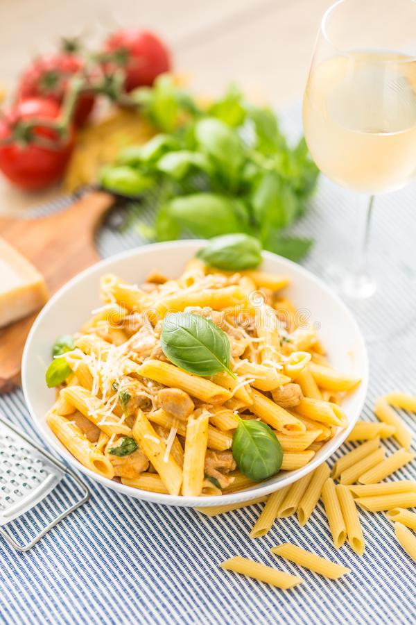 Pasta penne with chicken pieces mushrooms basil parmesan cheese and white wine. Italian food in white plate on kitchen. Pasta penne with chicken pieces mushrooms stock photos
