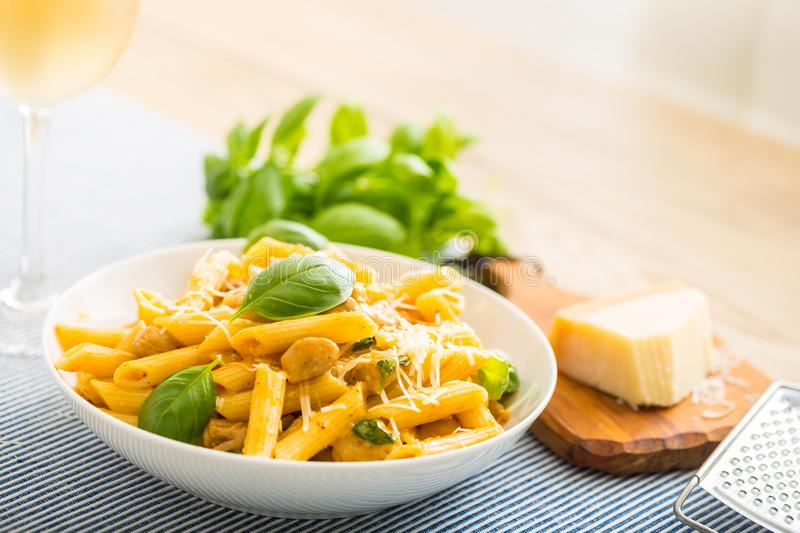 Pasta penne with chicken pieces mushrooms basil parmesan cheese and white wine. Italian food in white plate on kitchen. Pasta penne with chicken pieces mushrooms royalty free stock image