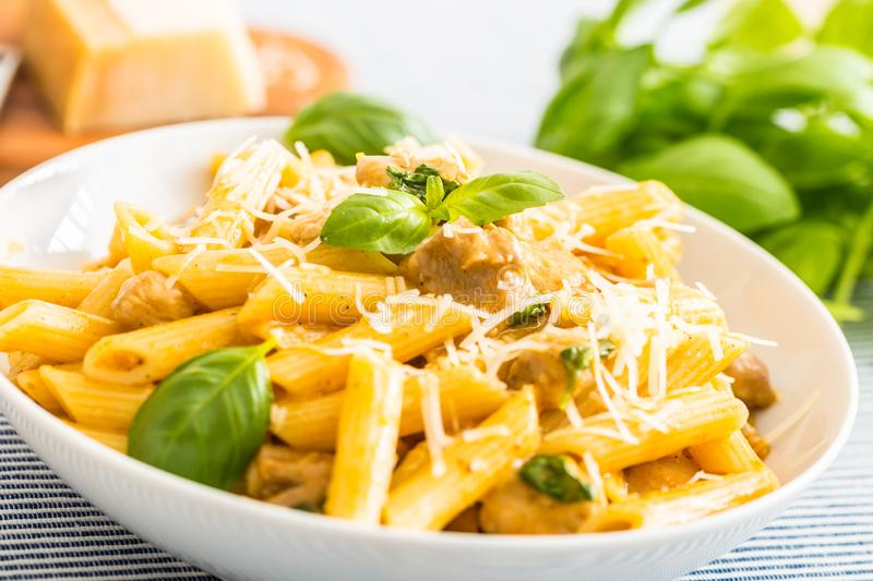 Pasta penne with chicken pieces mushrooms basil parmesan cheese and white wine. Italian food in white plate on kitchen. Pasta penne with chicken pieces mushrooms stock image